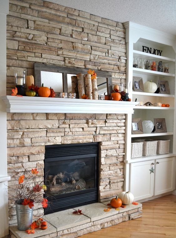 a mantel with faux leaves, birch branches, candles and pumpkins, a mirror to highlight them