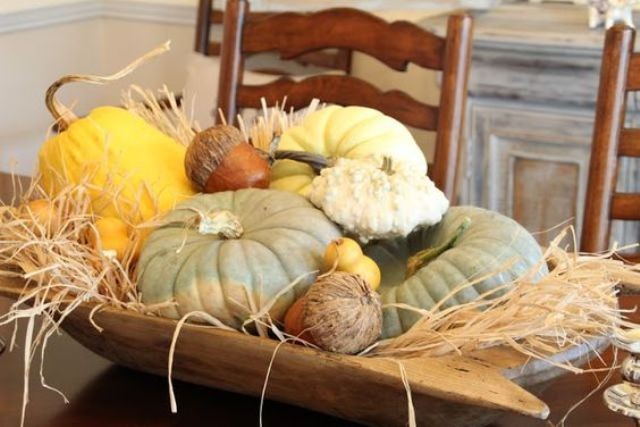a dough bowl with large pumpkins and gourds and faux acorns plus hay