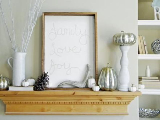 a modern mantel with silver pumpkins, pinecones, antlers and a sign looks fresh