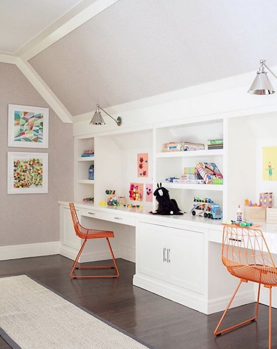 a whole wall is taken with white cabinetry and shelves and desks integrated for studying