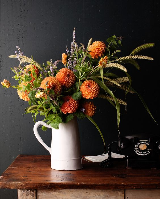 orange dahlias, greenery and grass, wheat and lavender in a jaug for a rustic feel