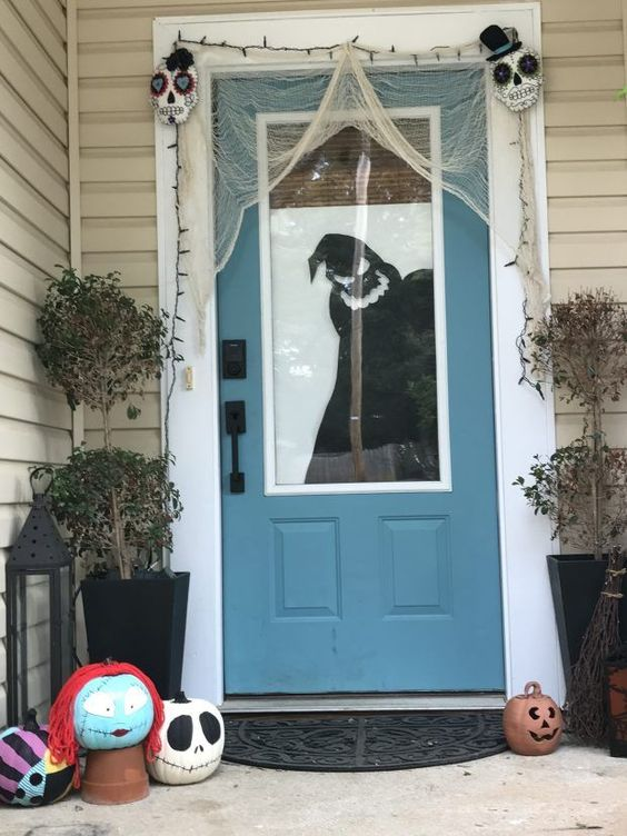 Nightmare Before Christmas porch and front door decor with a silhouette and pumpkins