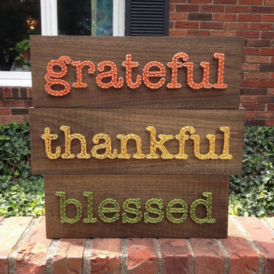 a Thanksgiving sign with three words in green, yellow and orange