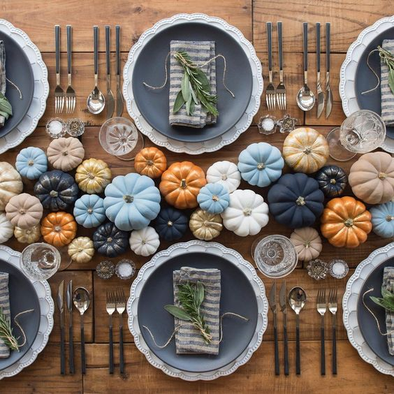 a modern and bold Thanksgiving table setting with colorful pumpkins in the center, matte black plates and greenery