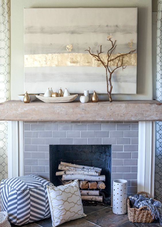 a modern mantel with white and gilded pears, branches and an abstract wall art with gold leaf