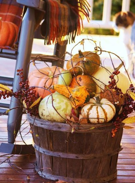a wooden basket outdoor arrangement with lots of faux pumpkins and gourds and faux berries and branches