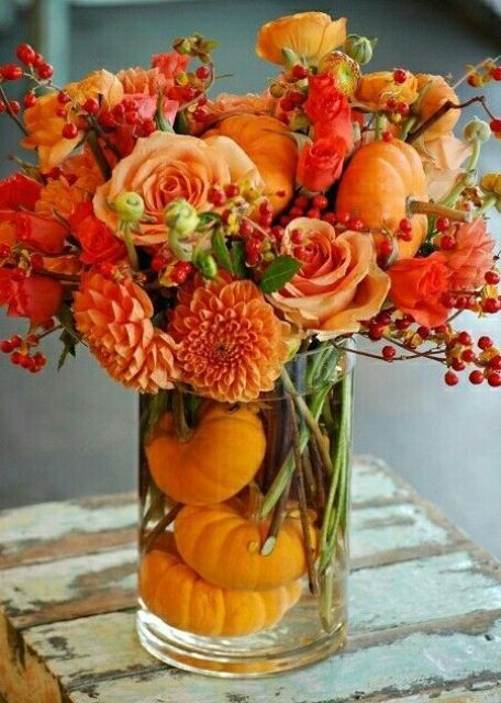 orange roses, berries, dahlias and orange pumpkins inside the vase for a monochromatic look