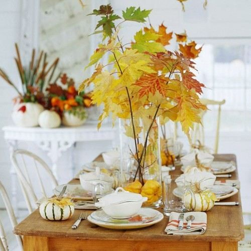 a natural tablescape with fall leaves and pumpkins, sheer vases and glasses