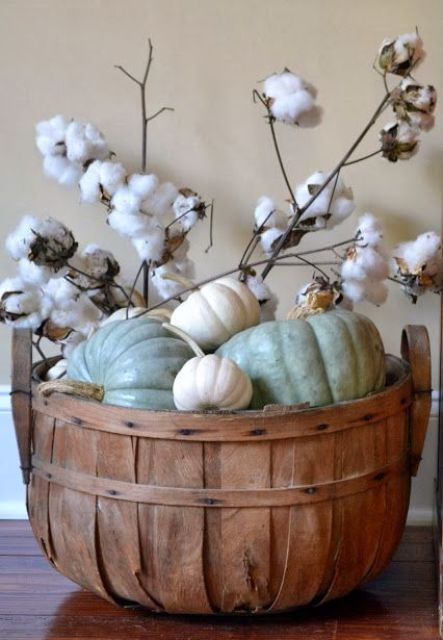 a wooden basket with white and green pumpkins and cotton branches for a neutral look
