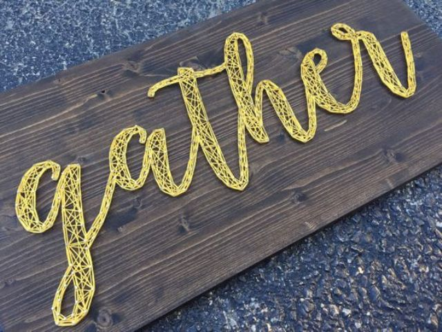 a wooden sign with 'gather' string word in yellow