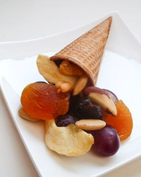 an ice cream cone cornucopia filled with nuts and candied fruits to serve dessert at a Thanksgiving party