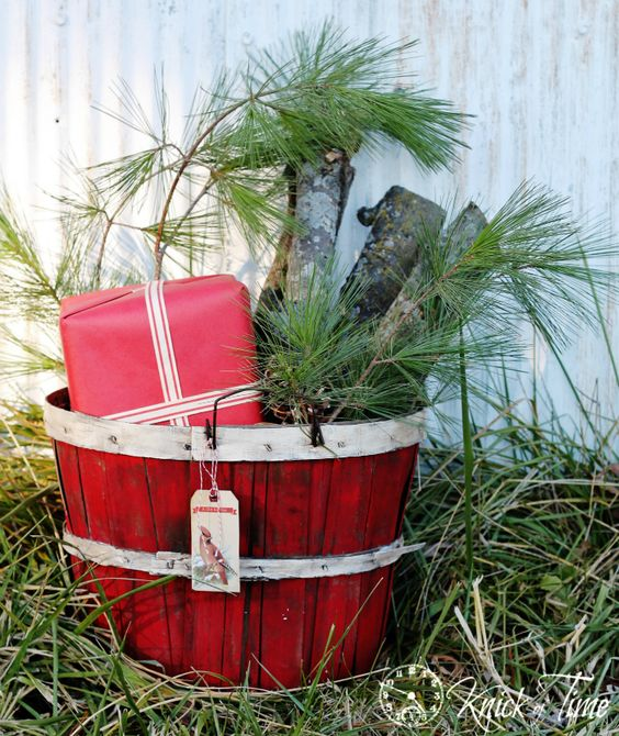 a bushel basket in red, pine branches, logs and a gift wrapped in red paper