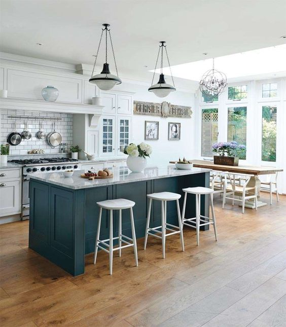 A Chic Emerald Kitchen Island With A Marble Countertop And A Breakfast Zone  On One Side