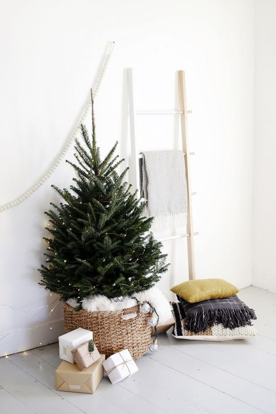 a small tree in a basket with white faux fur inside and lots of lights