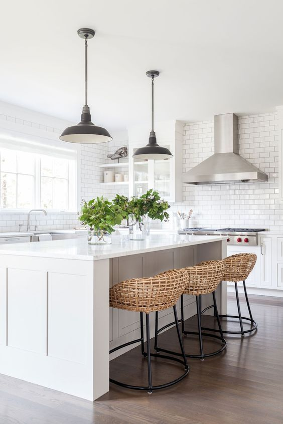 a breakfast zone on one side of the kitchen island and wicker stools for a cozy feel