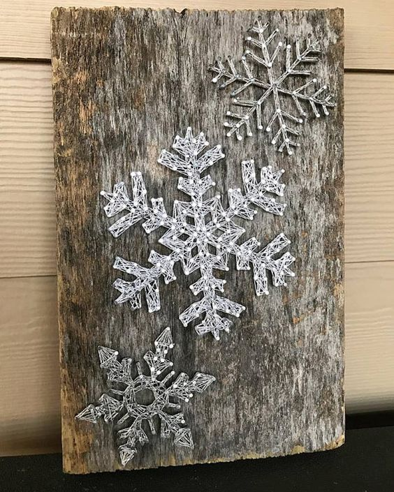 a reclaimed wood piece with string art silver snowflakes looks very cool