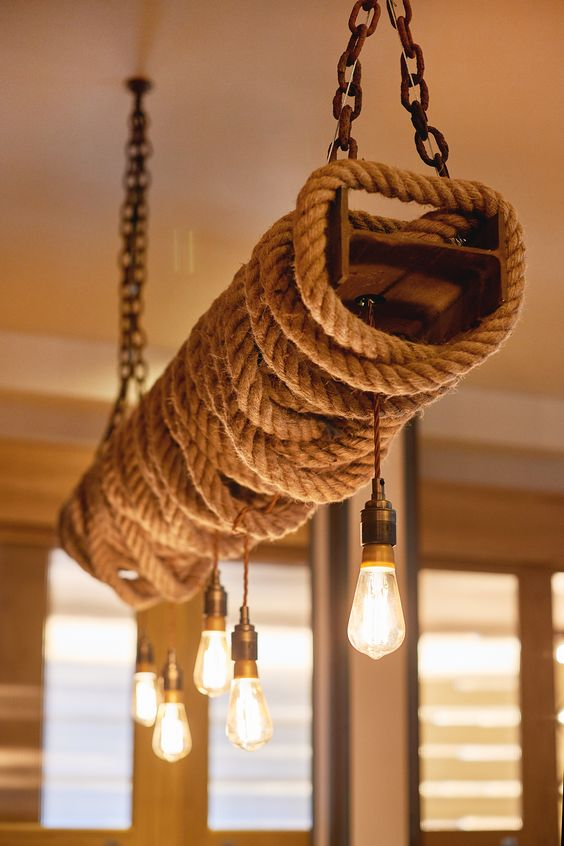 a rustic industrial piece of chain, rope, metal and bulbs for a bold space