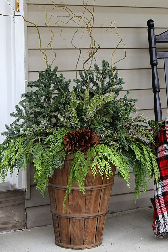 a bushel basket with evergreens and a large pinecone for decorating outdoors