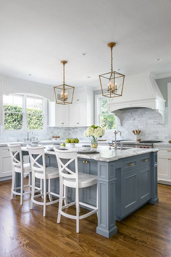 a coastal pale blue kitchen island with a breakfast space and white stools