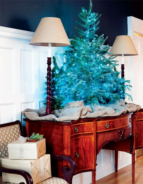 a mini tree decorated only with a turquoise light garland looks bold