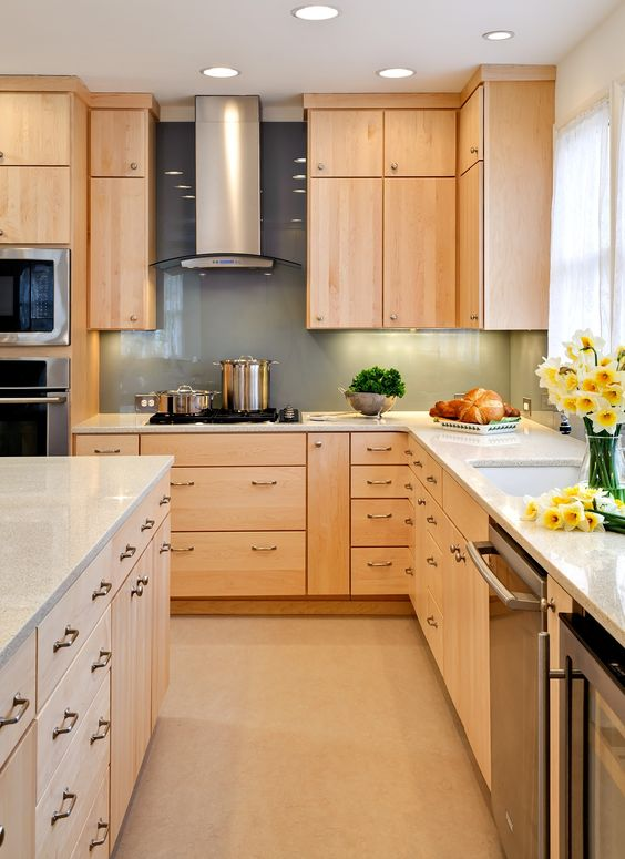 a modern kitchen with light-colored wood cabinets and a green glass backsplash