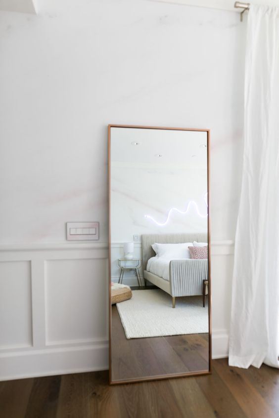 a modern mirror in a copper frame is always a fit for a modern bedroom
