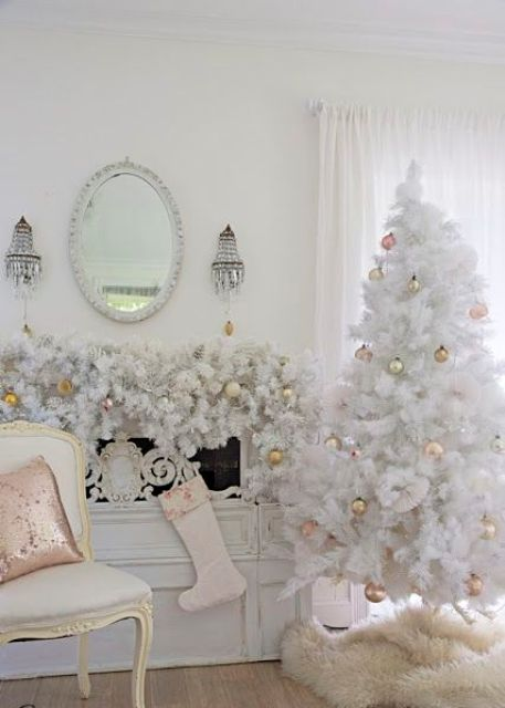 a white tree and a lush garland with mixed metal ornaments looks very refined