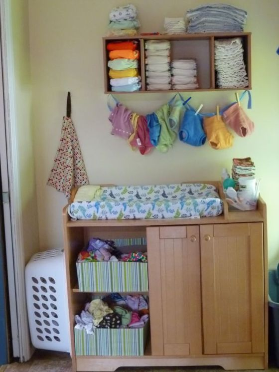 an open box shelf and some crates for diapers provide much storage