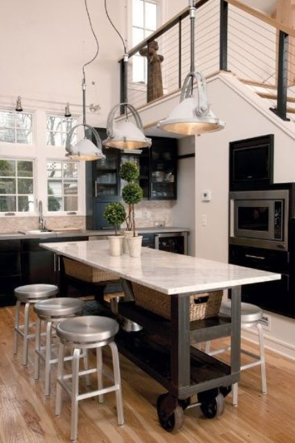 a kitchen island on casters with open shelving has two functions - a table and a cooking surface