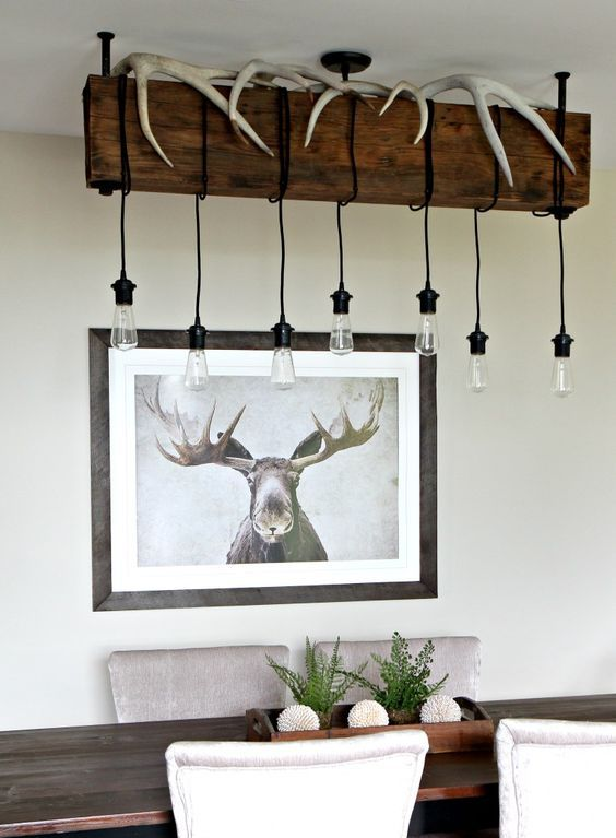 a wooden beam with antlers and bulbs hanging on cords for a rustic space
