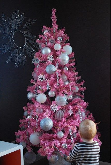 a bold pink Christmas tree with snowflakes and large silver ornaments