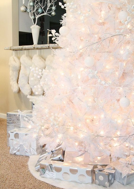 a white tree with white and silver ornaments and lights looks very chic and pretty