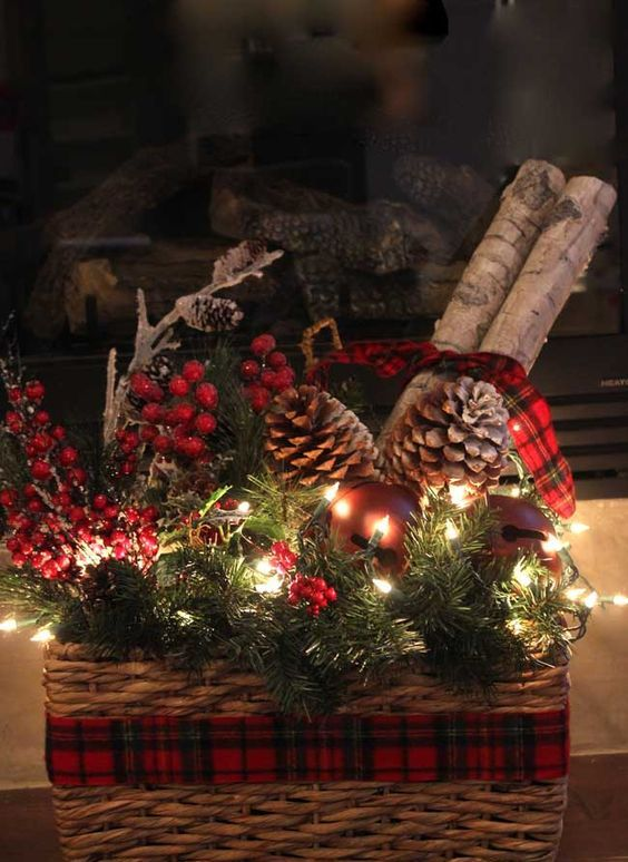 a basket with a plaid ribbon, pinecones, evergreens, berries, branches and jingle bells and LEDs