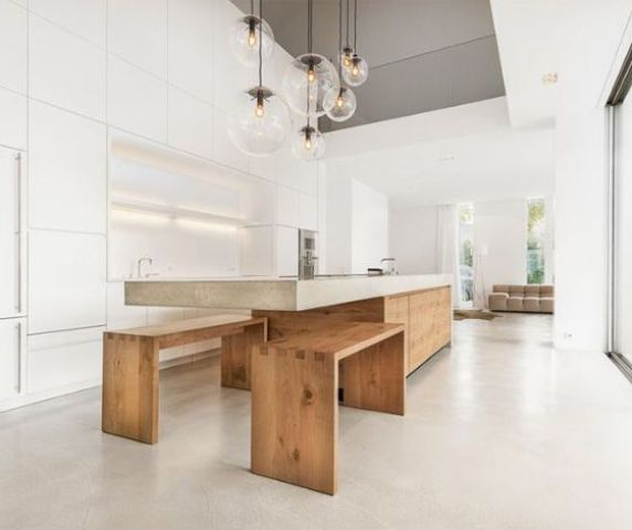 a minimalist concrete kitchen island with an eating space and benches under it