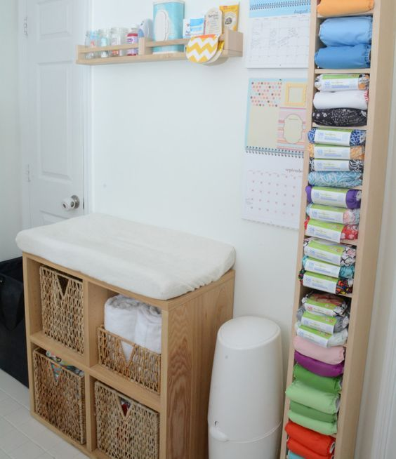 a tall vertical shelf for storing diapers next to the changing table