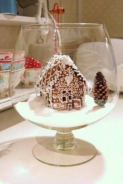 a Christmas terrarium with a glazed gingerbread house, fake snow and a pinecone