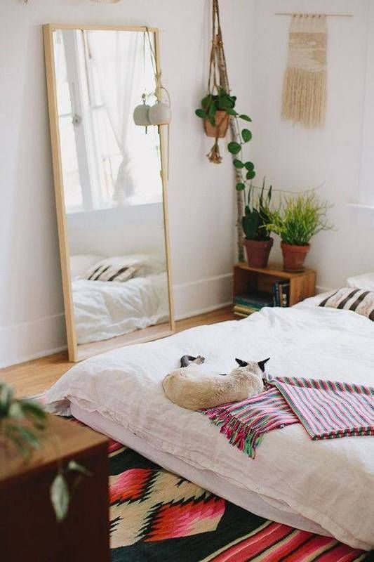 a mirror in a light-colored wooden frame for a boho-chic bedroom