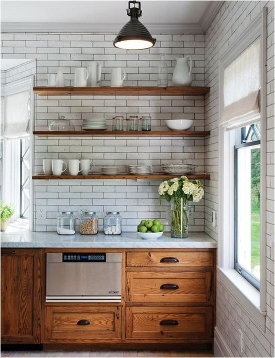 a modern farmhouse kitchen with rich-colored wooden cabinets and shelves and subway tiles