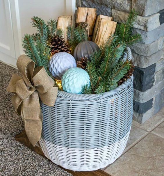 a basket with Christmas ornaments, firewood, evergreens and pinecones, LEDs inside