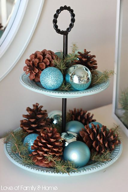 a cupcake stand with evergreens, pinecones, turquoise and silver ornaments for a rustic feel