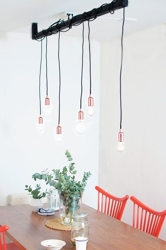 a cute industrial chandelier of a metal pipe and multiple copper bulbs for a Scandinavian space
