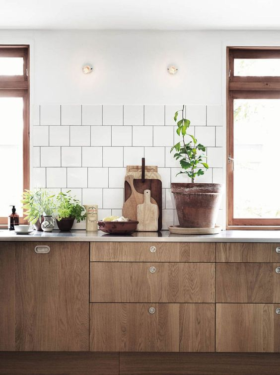 a modern rustic space with reclaimed wood cabients and simple white tiles on the walls