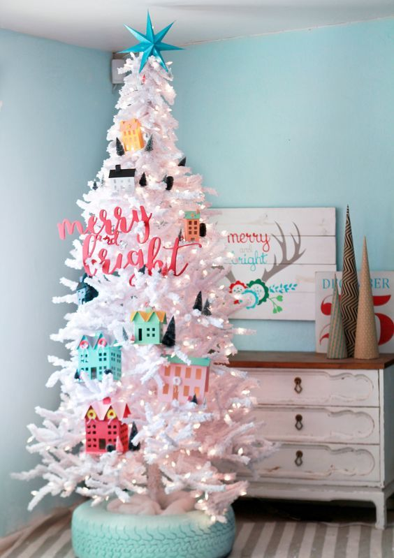 a white tree decorated with colorful houses and mini trees for a fun touch in a