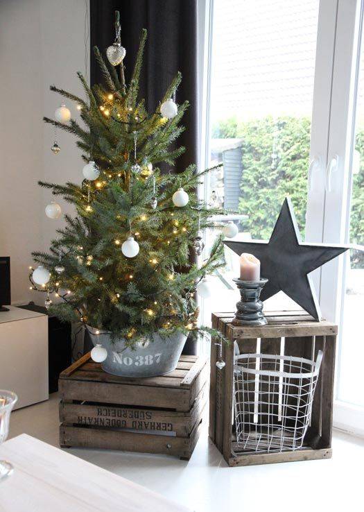 a Christmas tree in a bucket, with lights and silver and white ornaments