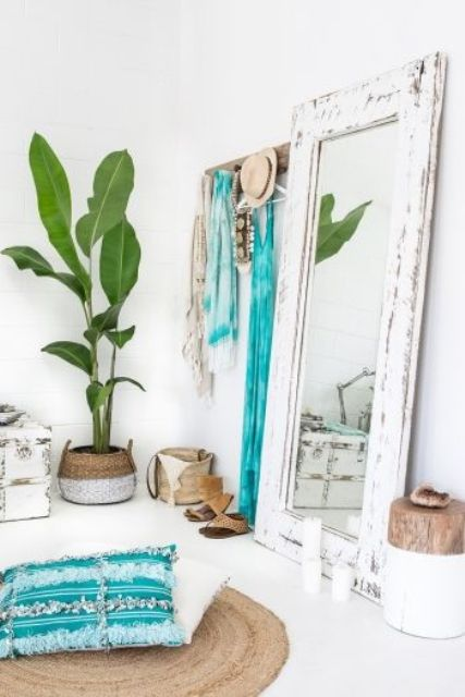 a boho beach bedroom with a mirror in a white shabby chic frame