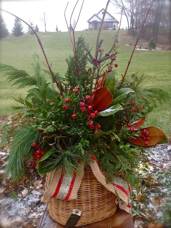 a lush basket with evergreens, berries, foliage and festive ribbons for outdoor decor