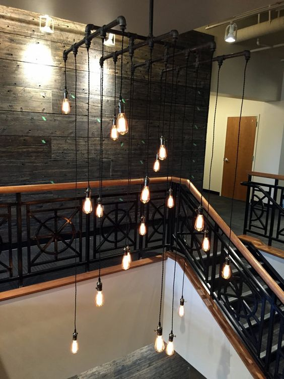 highlight your high ceilings and a staircase with a large black metal tubing and bulbs on cords
