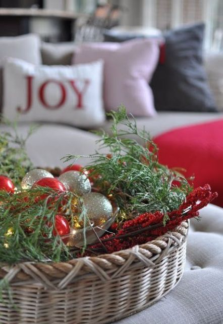 a basket with Christmas ornaments, greenery and berries for indoor decor