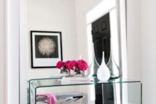 11 a modern glam entryway with a large floor mirror and a glass console for an ethereal look