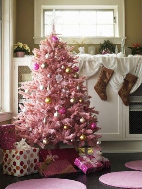 a pastel pink Christmas tree with metallic and fuchsia ornaments